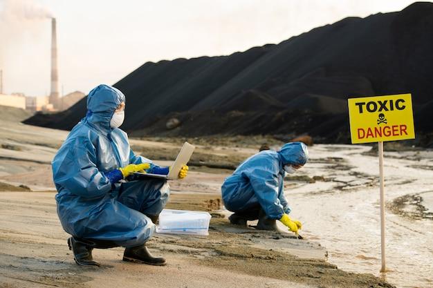 Исследователь спецодежды, описывающий характеристики загрязненной воды и почвы.