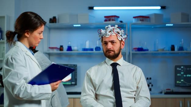 脳波スキャンヘッドセットで脳スキャンを行う前に、クリップボードにメモを取りながら男性の症状を尋ねる神経内科医の医師。健康状態、神経系、断層撮影スキャンを分析する科学者