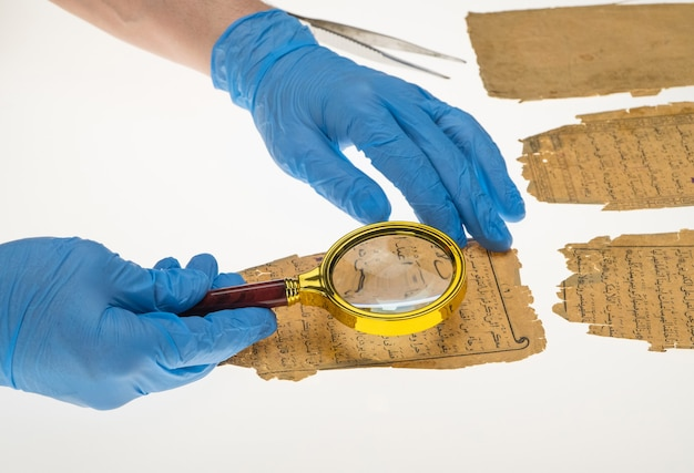 A researcher studies arabic writing from the koran using a magnifying glass paleography