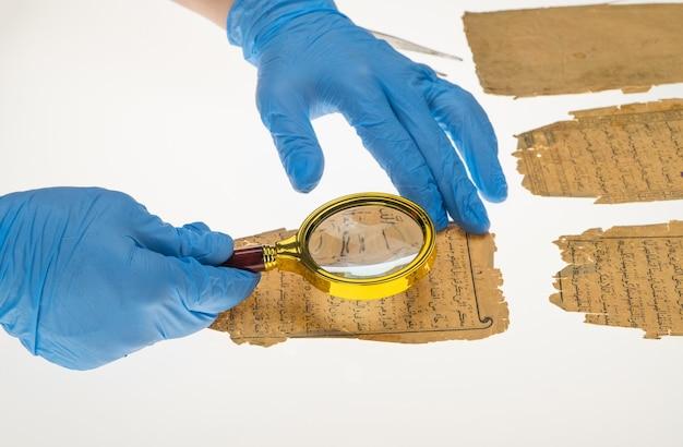 研究者は、拡大鏡とライト付きのテーブルを使用して、コーランからのアラビア文字を研究します
