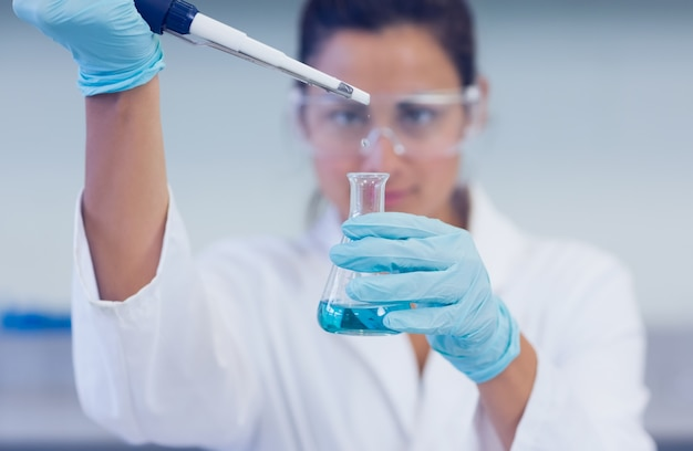 Researcher with blue liquid in flask and pipette in lab