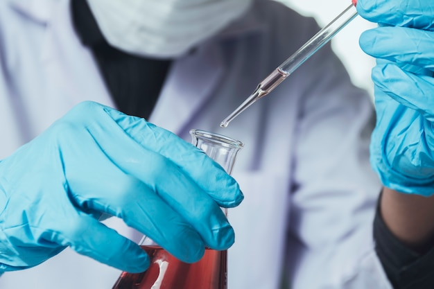 Researcher with glass laboratory chemical test tubes with liquid for analytical, medical
