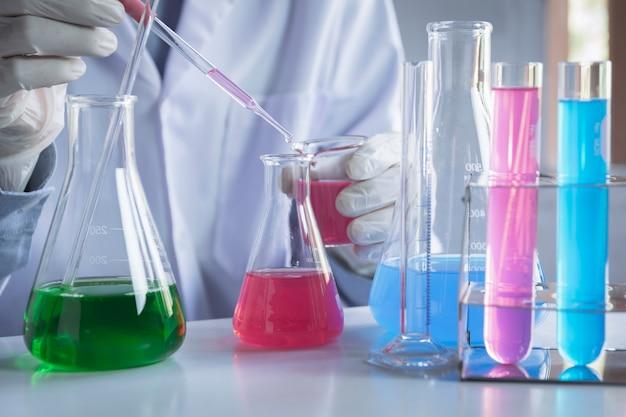 Исследователь со стеклянными лабораторными химическими пробирками с жидкостью для аналитических, медицинских, фармацевтических и научных исследований концепции.