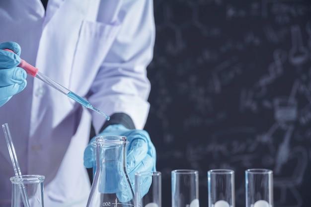 Исследователь со стеклянными лабораторными химическими пробирками с жидкостью для аналитических, медицинских, фармацевтических и научных исследований.