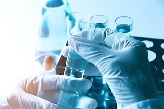 Researcher with glass laboratory chemical test tubes with liquid