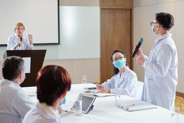 彼女が会議で発表している新しいワクチンの仕事の原則についてスピーカーに尋ねるマイクを持った研究者