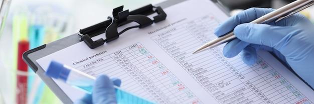 Исследователь записывает химические параметры жидкости в документ концепции химического исследования.