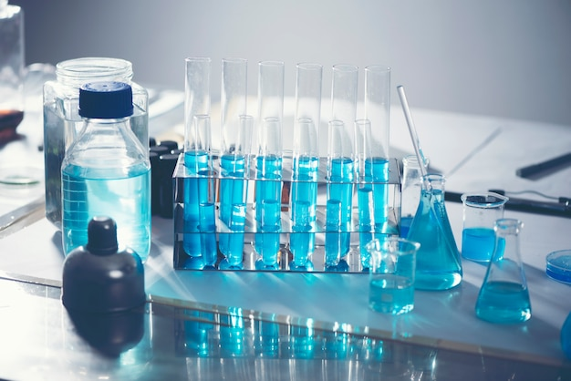 Researchers are using glassware and blue solutions in laboratories