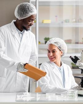 Исследователи в лаборатории биотехнологии с микроскопом и планшетом