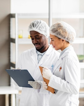 Исследователи в лаборатории биотехнологии с планшетом и буфером обмена