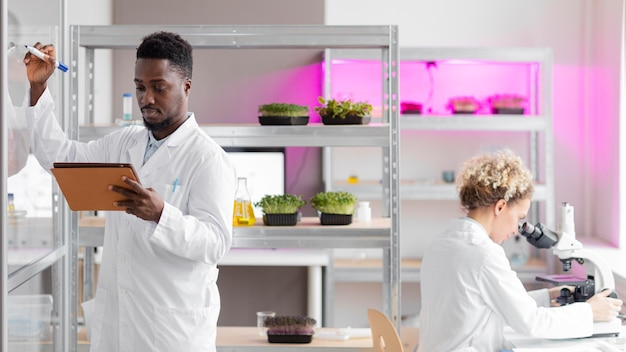 태블릿과 현미경을 갖춘 생명 공학 실험실 연구원
