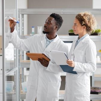 Исследователи с планшетом и буфером обмена в лаборатории биотехнологии