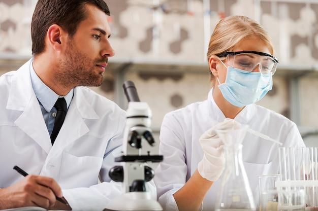 과학 실험실에서 연구. 실험실에 앉아 실험을 하는 두 젊은 과학자의 낮은 각도 보기