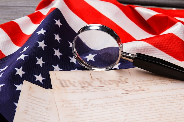 Researching the declaration of independence. glass magnifier with text and flag of the usa.