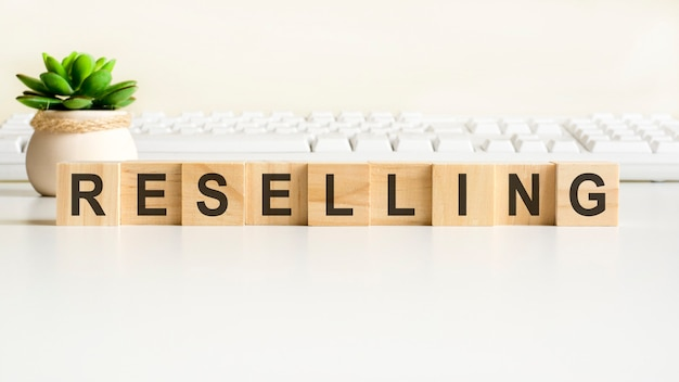 Reselling word made with wooden blocks. front view concepts, green plant in a flower vase and white keyboard on background