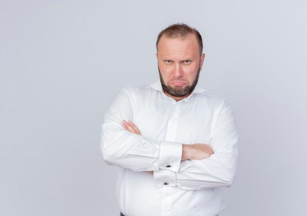白い壁の上に立っている腕を組んで真面目な顔で白いシャツを着て憤慨しているひげを生やした男