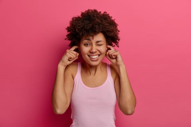 憤慨している不快な暗い肌の女性は、指で耳を塞ぎ、非常に大きな音を無視し、顔を眉をひそめ、歯を見せ、騒音に耐えられず、目をまばたきし、カジュアルな服を着て、ピンクの壁に隔離されます