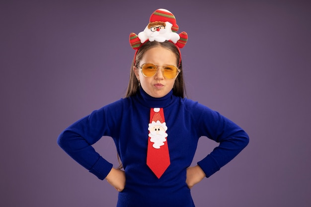Resentful  little girl in blue turtleneck with red tie and  funny christmas rim on head  looking at camera with frowning face with arms at hip standing over purple background