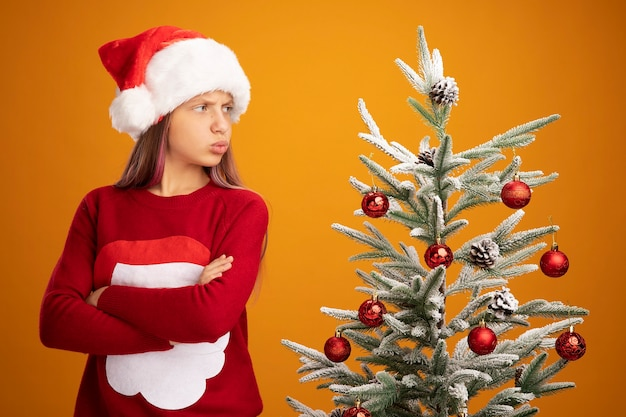 Resentful little girl in christmas sweater and santa hat standing next to a christmas tree looking at it with frowning face with arms crossed over orange background