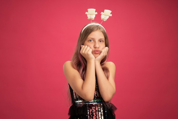 Resentful little girl in glitter party dress and funny headband looking at camera blowing cheeks new year celebration holiday concept standing over pink background