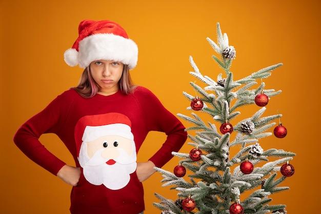 オレンジ色の背景の上のクリスマスツリーの横に立っているヒップで腕と怒っている眉をひそめている顔でカメラを見てクリスマスセーターとサンタ帽子の憤慨している少女