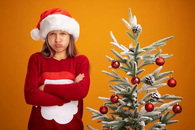 크리스마스 스웨터와 산타 모자에 분개 어린 소녀 팔을 찡그린 얼굴로 카메라를보고 오렌지 배경 위에 크리스마스 트리 옆에 서 넘어