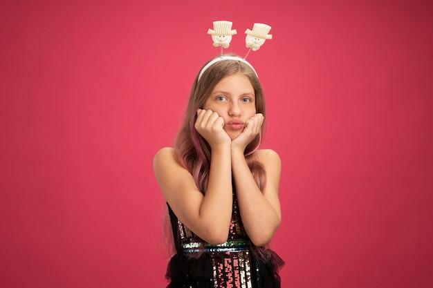 キラキラパーティードレスとピンクの背景の上に立っているカメラ吹く頬新年のお祝いの休日の概念を見て面白いヘッドバンドで憤慨している少女