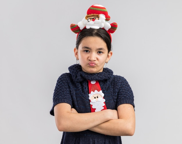 腕を組んで怒った顔で見て頭に面白いクリスマスの縁と赤いネクタイを着ているニットドレスの憤慨している少女