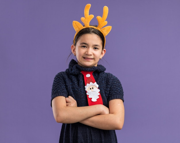 Resentful little girl in knit dress  red tie with funny rim with deer horns on head   with arms crossed  standing over purple wall