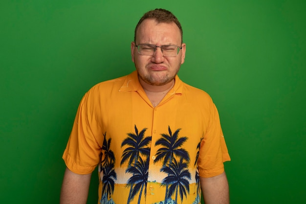 Resentful man in glasses and hawaiian shirt with sad expression pursing lips standing over green wall