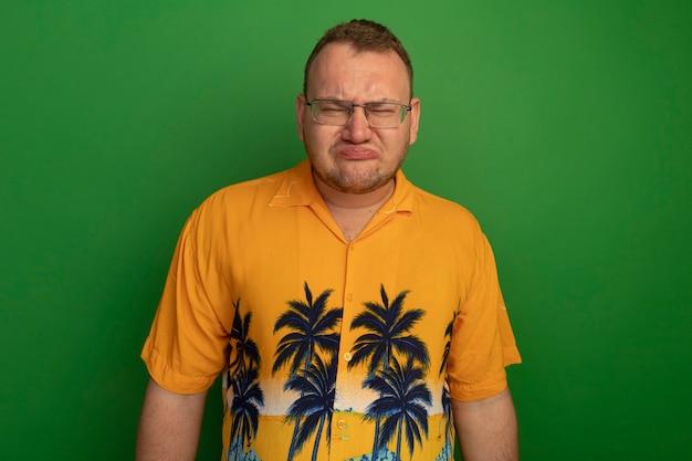 緑の壁の上に立っている唇をすぼめる悲しい表情とメガネとアロハシャツの憤慨した男