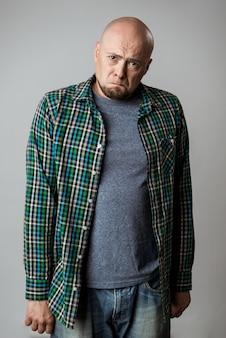 Resentful sad emotive man in shirt posing over beige wall
