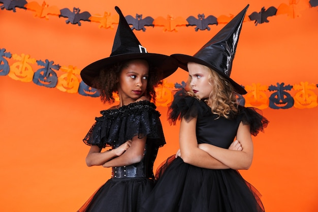 Resentful witch girls in black halloween costume looking at each other isolated over orange pumpkin wall