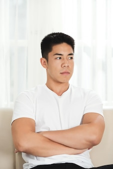 Resentful young asian man sitting on couch with crossed arms