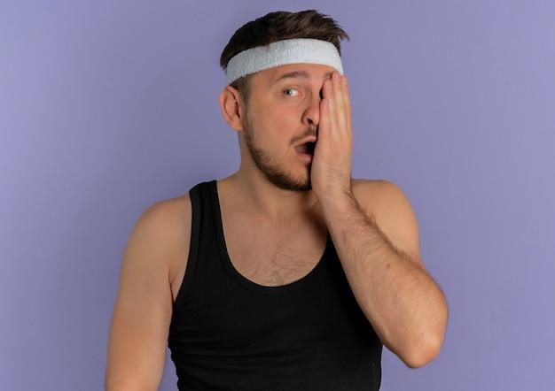 보라색 배경 위에 서있는 한쪽 눈 wirh 팔을 덮고있는 머리띠와 분개 한 젊은 피트니스 남자
