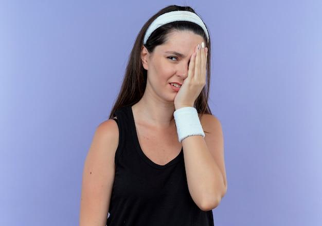 青い壁の上に立っている腕で片目を覆っている側を探しているヘッドバンドの憤慨している若いフィットネス女性