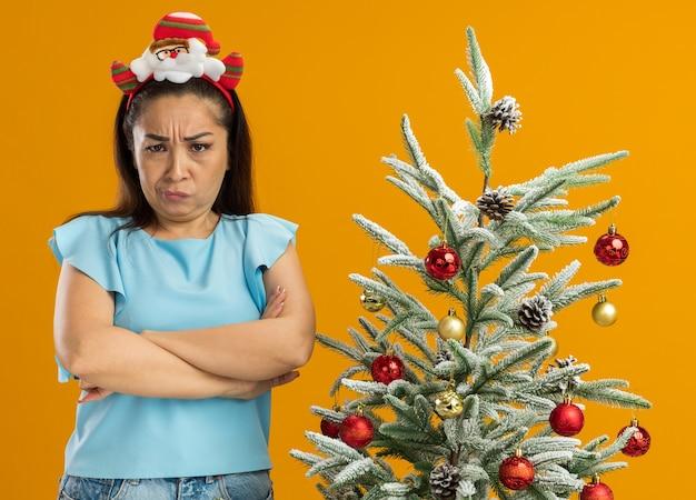Risentita giovane donna in blu in alto indossando divertenti natale cerchio sulla testa guardando la fotocamera con la fronte accigliata con le braccia incrociate in piedi accanto a un albero di natale su sfondo arancione