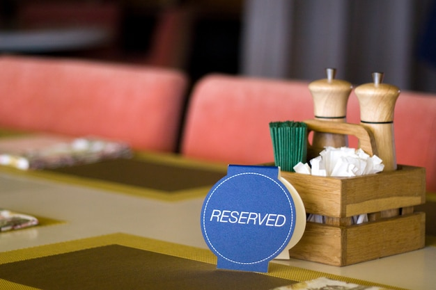 Reserved card for reservation seat at restaurant - leisure, people and service concept