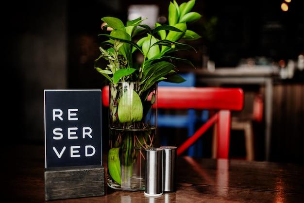 Зарезервированный знак на столе в ресторане. красный стул и ваза. горизонтальный вид нескольких объектов.
