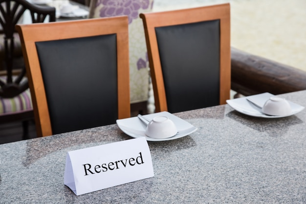 Reserved sign on restaurant table with chair