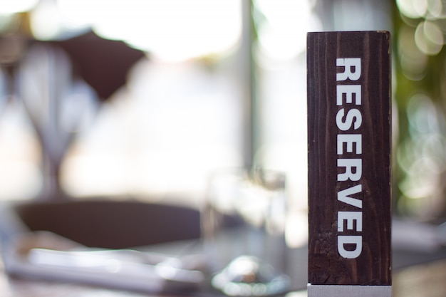 Reserved wooden card on blurry background reservation at restaurant- leisure and service c