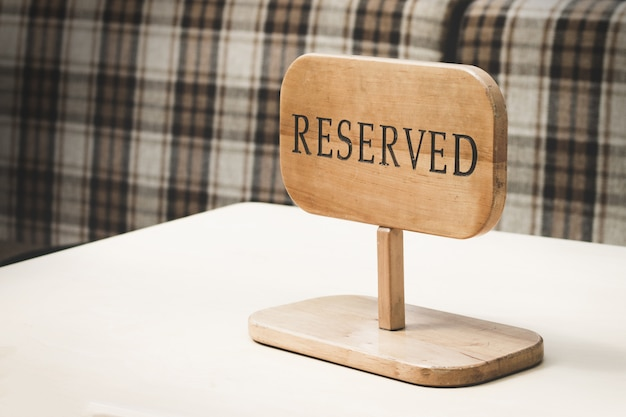 Reserved wooden sign on top of table in a restaurant