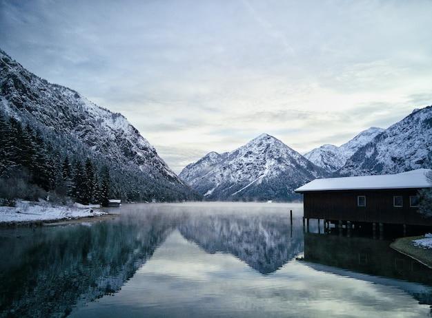 雪に覆われた美しい岩山に囲まれた湖の近くの住宅