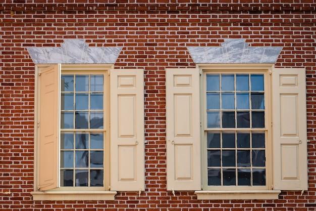 赤レンガの壁に開いたシャッター付きの住宅の窓