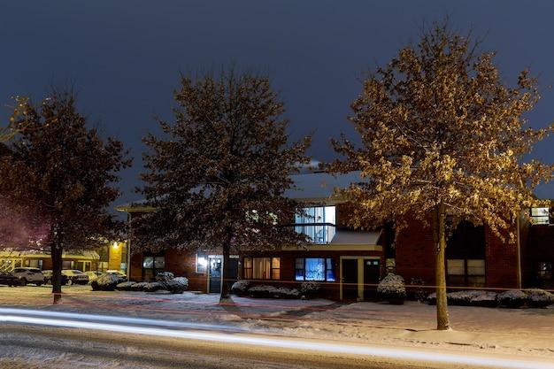 住宅地と駐車場の夕方の照明付きの家と雪の中の道路