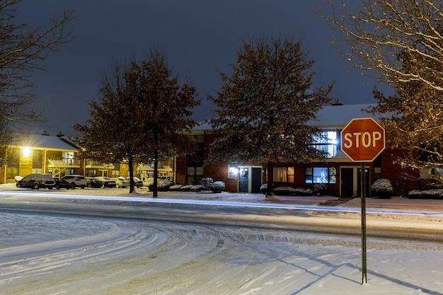 雪道に照らされた冬の夜の街並みに雪が降る住宅街と駐車場