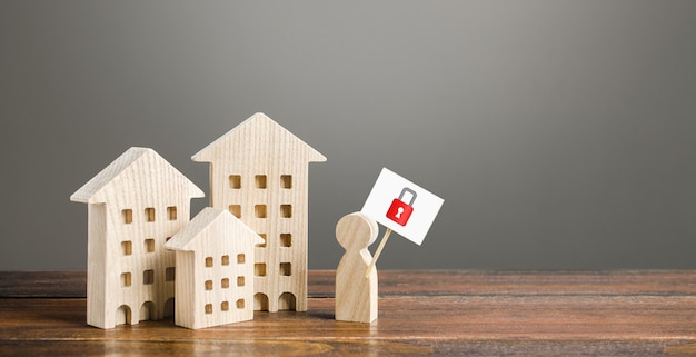 Residential buildings and man holding red padlock sign.