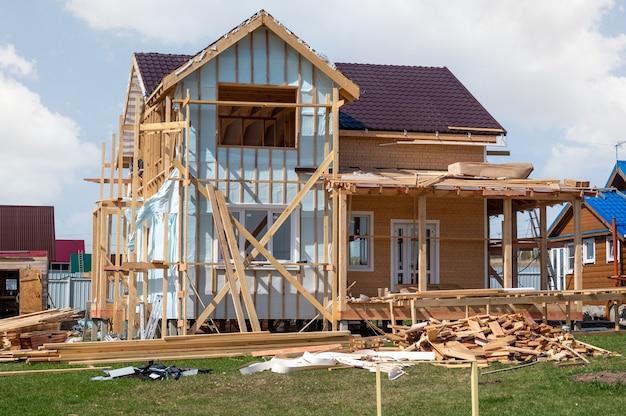 건설 중인 주거용 컨트리 하우스. 마지막 단계에서 별장 건설. 흐린 하늘 아래 비계와 건물 건설