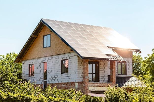 Жилой частный дом с солнечными батареями на крыше под строительство