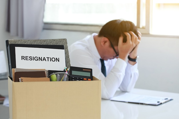 Resignation concept personal belongings and files in a brown cardboard box with resignation letter